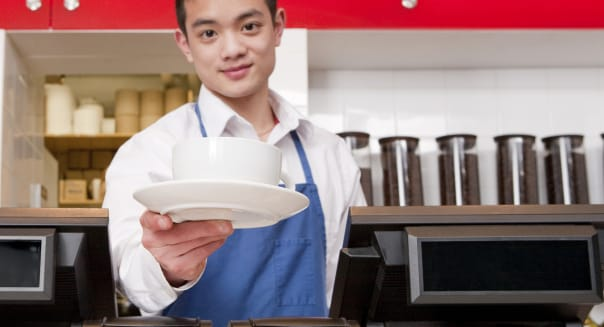 Asian male barista holding coffee out