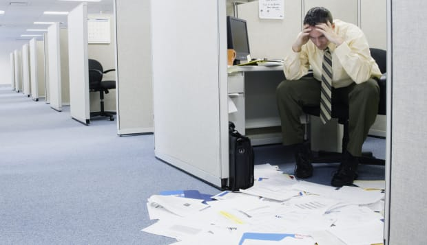 Man sitting on chair looking at document on floor