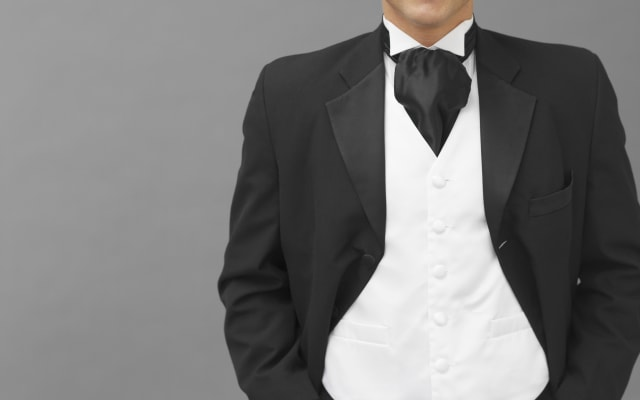 portrait of a groom standing with his hands in his pockets