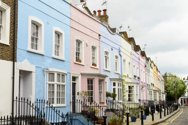 A colourful row of pastel painted Victorian townhouses in Chelsea, London.