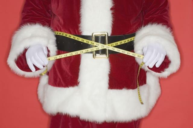 Santa Claus measuring waist with tape measure