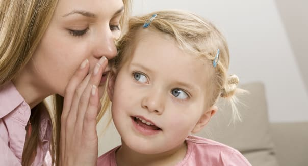 Mother whispering in daughter's (2-3) ear, close-up