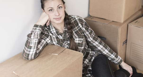 Portrait of young woman relaxing after moving into new house