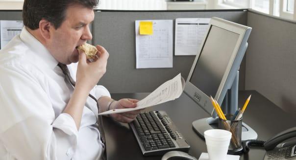 Business man eating at desk