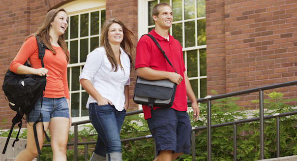 Subject: A group of college students Walking to class in a university campus with book bags on their shoulders.
