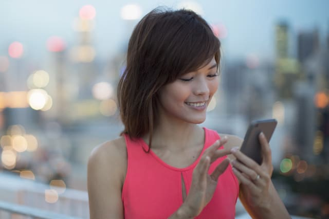 Woman using handphone with city in background