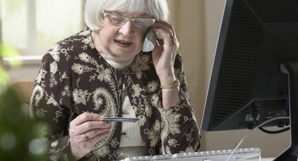 elderly woman using credit card over the phone