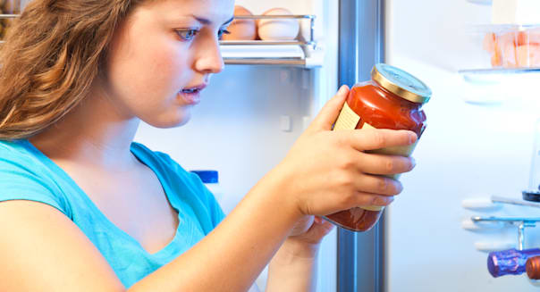 Woman Studying and Reading Food Label in Front of Refrigerator