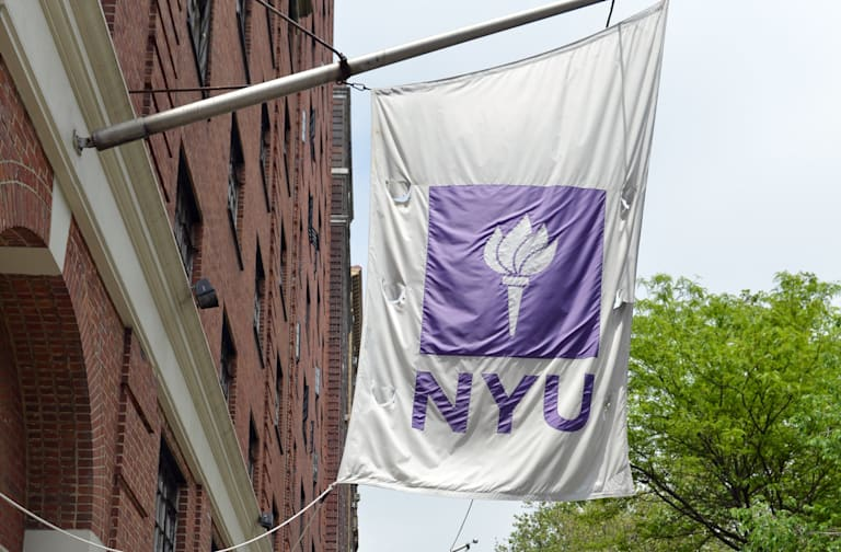 Flags fly from a New York University bui