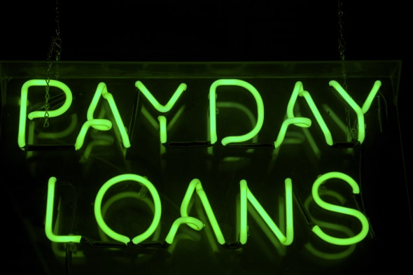 Payday Loans sign glows in green neon on a black background