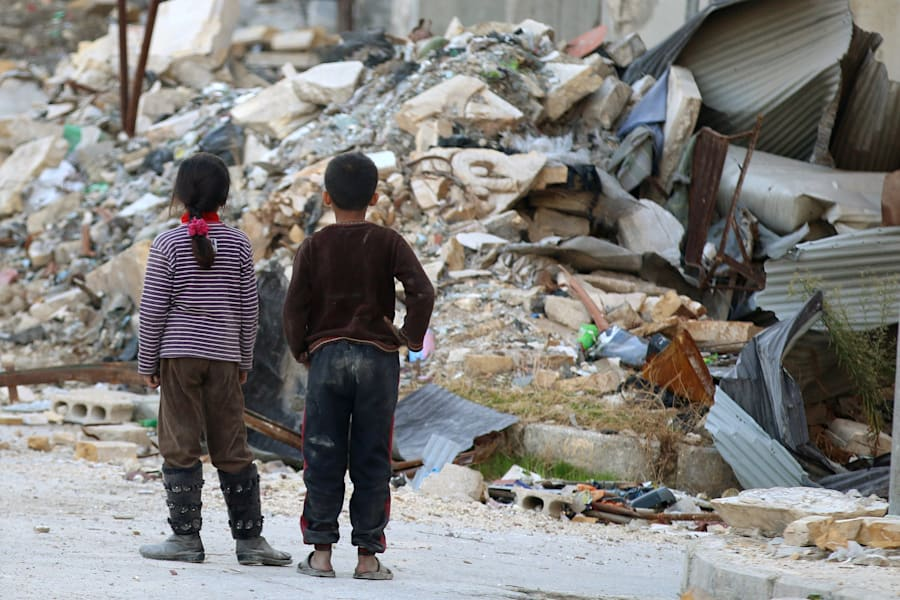 Children inspect rubble of damaged buildings in a rebel-held besieged area in