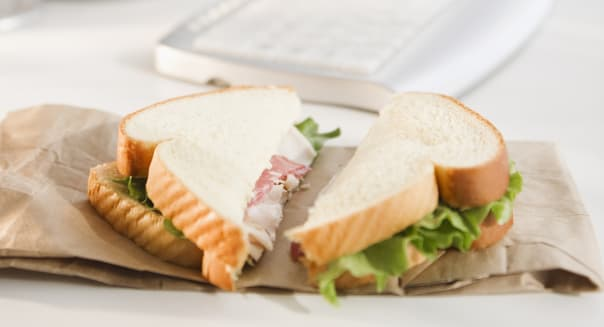 Sandwich on brown bag beside computer