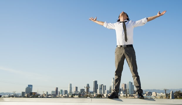 Mixed race businessman standing on urban rooftop