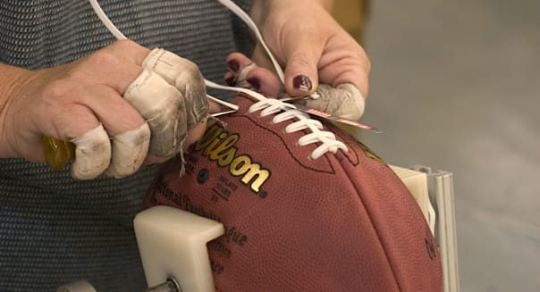 Workers manufacture footballs at Wilson Sports factory