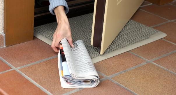 woman picking up morning paper...