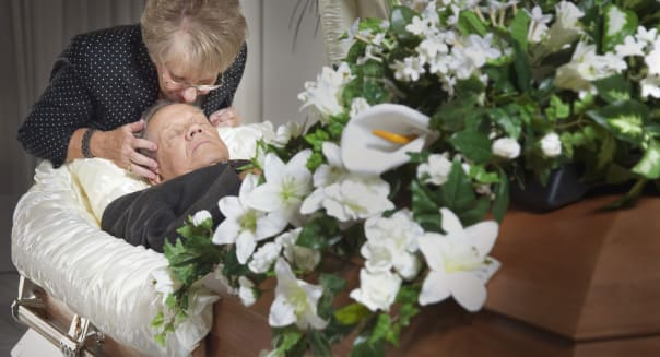 Woman Kisses Her Deceased Spouse In A Coffin