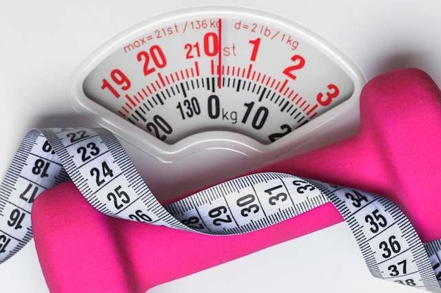 healthy lifestyle fitness weight control concept. Closeup pink dumbbell with measuring tape on white scales