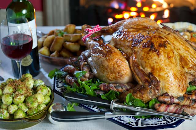 A Christmas or Thanksgiving roast turkey meal,roast potatoes and vegetables,seen in front of a open period fire.a UK food Xmas