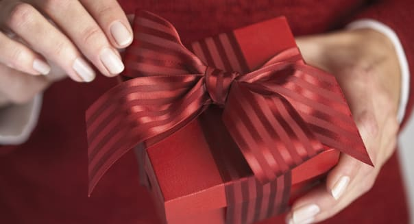 Woman Adjusting Bow on Gift