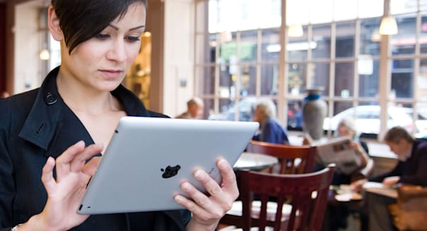 Young woman browsing the Internet on an Apple iPad tablet computer using free coffee shop wi fi, London, England, UK
