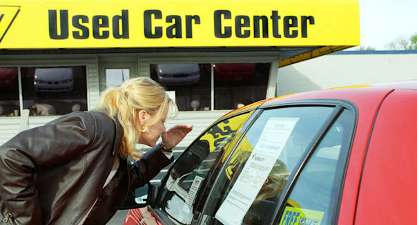 AMTD88 College age female shops for a used automobile and looks at the sticker price of the car on a used car lot College; age;