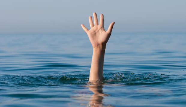 single hand of drowning man in...