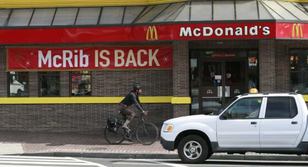 A man bicycles past a McDonald's restaur