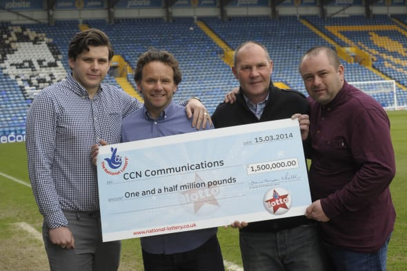 Handout photo issued by Camelot of the CCN Communications syndicate members (left to right)  Lewis Fox, Tom Fox,  Mark Bush and Sid Veness cas they celebrate their jackpot win at Fratton Park, Portsmouth of ?1,558,848, one of four lucky ticket holders from the Lotto draw last Saturday.  PRESS ASSOCIATION Photo. Picture date: Wednesday March 19, 2014. See PA story LOTTERY Engineers. Photo credit should read: Ady Kerry/Camelot                    /PA WireNOTE TO EDITORS: This handout photo may only be used in for editorial reporting purposes for the contemporaneous illustration of events, things or the people in the image or facts mentioned in the caption. Reuse of the picture may require further permission from the copyright holder.