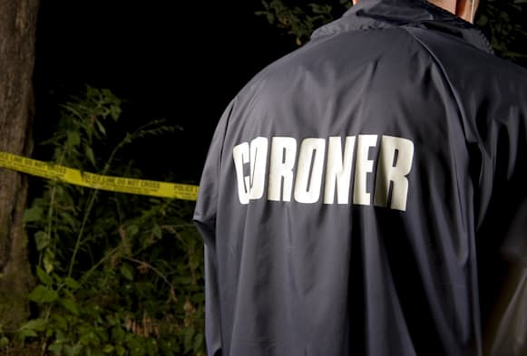 'A coroner at a crime scene in the bush / forest. There is police tape blurred in the background.As always, my images are proces