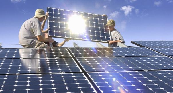Men installing solar photovoltaic panels at sunset