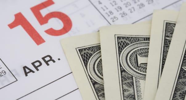 Dollar bills on an April 15th calendar page