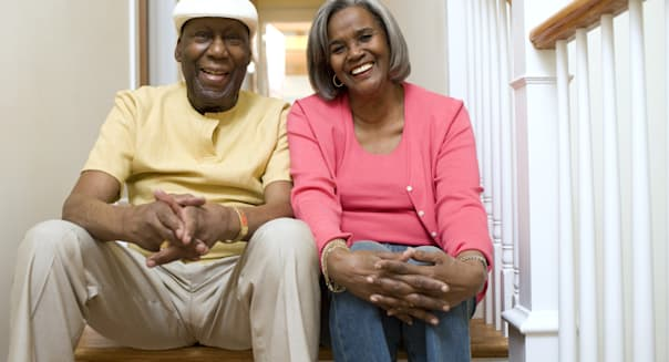 Mature couple sitting on hall stairs at home