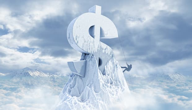Caucasian man climbing dollar sign on mountaintop