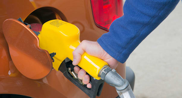 Man pumping gas into his vehicle at service station