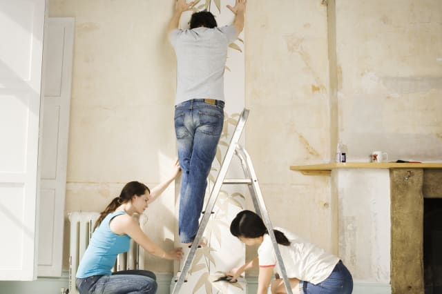 Two women and one man hanging wall paper