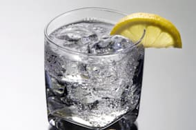 Club soda or Vodka / Gin and tonic mixed drink with lemon slice on a gray background with reflection