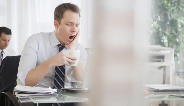 Caucasian businessman drinking coffee and yawning