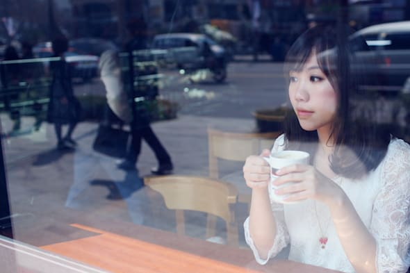 A young lady in a white lace dress was having her coffee before the windows of a coffee shop. The photographer was outside the w