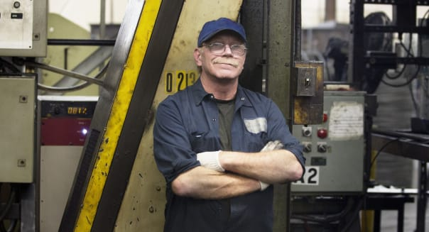Factory Worker with Arms Crossed by Machinery