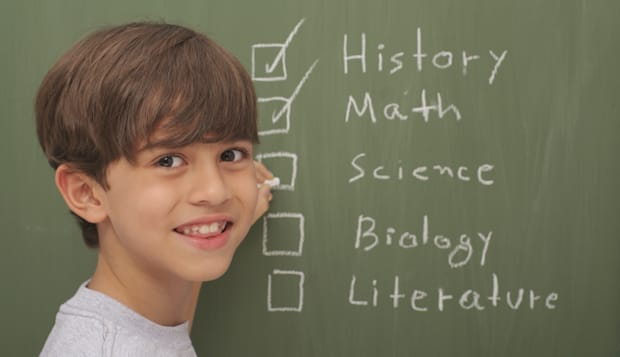 Kid in front of blackboard checking a list of educational subjectsSome other related images: