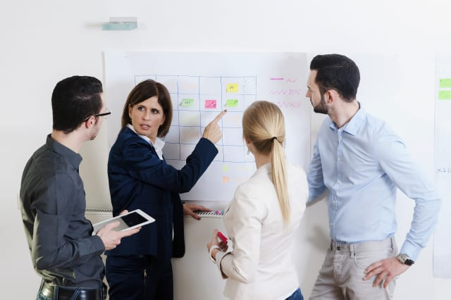 Group of young business people and mature businesswoman in discussion in office, Germany
