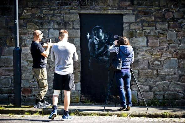 People photograph and film the latest officially confirmed Banksy artwork, named Mobile Lovers, featuring a man and a woman embraced and looking at their mobile phones, which is sprayed onto a black wooden board in a blocked off doorway on Clement Street, Bristol, within sight of the city's bustling centre. PRESS ASSOCIATION Photo. Picture date: Tuesday April 15, 2014. The latest artwork to be officially confirmed by Banksy has been tracked down to a street in the street artist's hometown. It comes days after a piece depicting three 1950s-style agents listening in on conversations in a telephone box appeared on a house in Cheltenham, Gloucestershire. Website streetartnews described the Bristol piece as