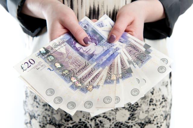 happy girl holding fan of cash...