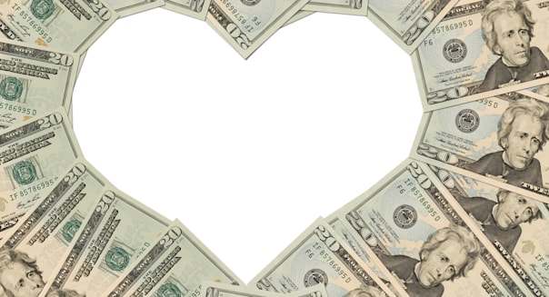 Twenty dollar bills making a heart symbol on a white background, money heart; Shutterstock ID 70737931; PO: Money heart; Job: DF