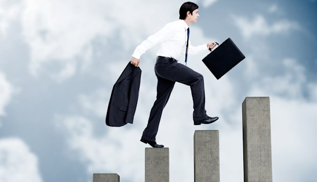 Young businessman climbing grey steps