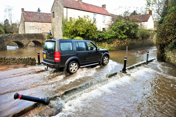 Land Rover Discovery drives through a flood