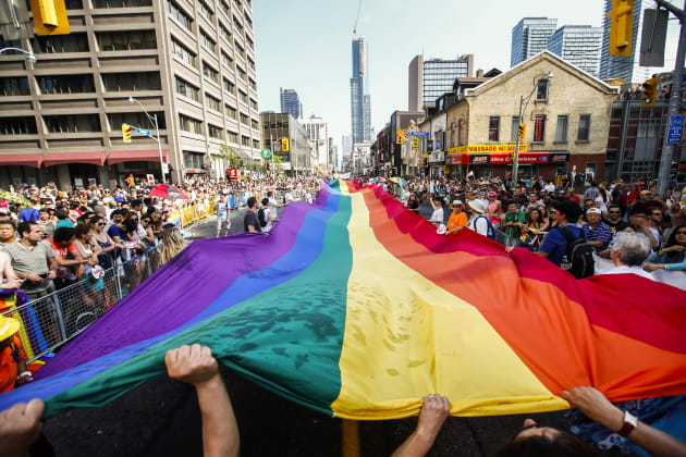 """Revellers hold a giant pride flag during the """"WorldPride"""" gay pride Parade in Toronto, June..."""