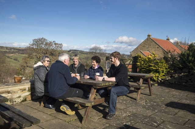 Embargoed to 0001 Friday March 3 Customers enjoy a drink in the beer garden at the George and Dragon pub in Hudswell, North Yorkshire, which has been crowned the CAMRA Pub of the Year.