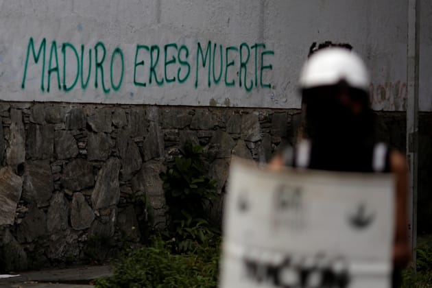 """Graffiti that reads """"Maduro is death"""" is seen next to a roadblock during a strike called to..."""