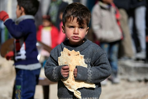 A displaced boy carries bread at a shelter in Jibreen, on the outskirts of Aleppo, Syria February 1,